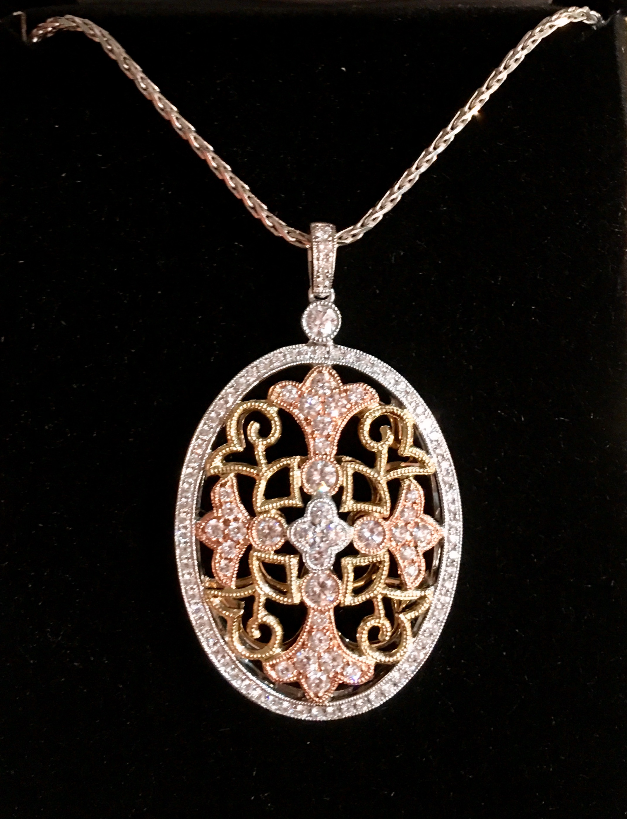 This 14k tricolor pendant is set with 105 round diamonds with a combined total weight of 1.07cts in graceful filigree.